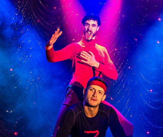 Two men in gaudy lycra outfits pose comically one behind the other on a brightly lit stage