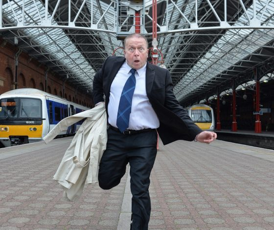 a man in a dark suit and tie runs along a train platform towards the camera with a comically dramatic facial expression