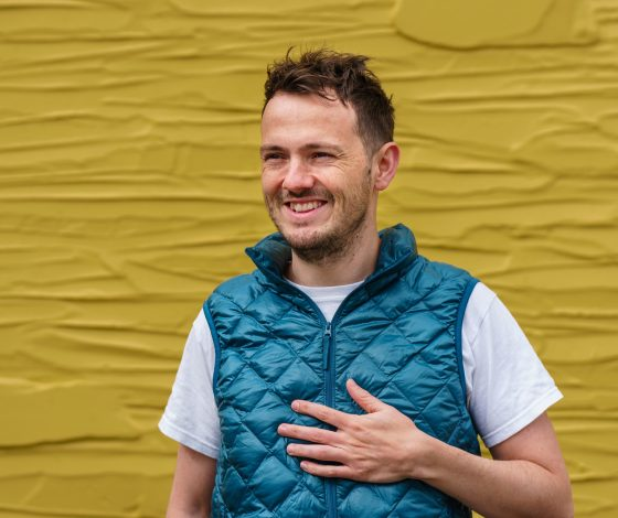A young man smiles wearing white t-shirt under a blue gilet, dark yellow background