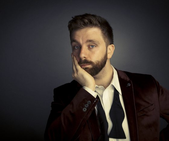 A man with a neat beard wearing a smoking jacket poses with a wan expression and a hand raied up to his chin