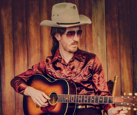 A man in country and western clothes and a stetson hat and shades sits on a stool strumming an acoustic guitar