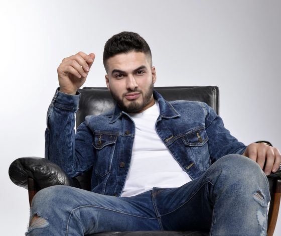 A smartly groomed young man wearing denim reclines on a leather chair