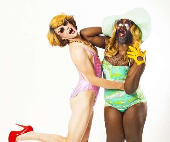 Two fabulous drag performers in wigs and one-piece swimwear.