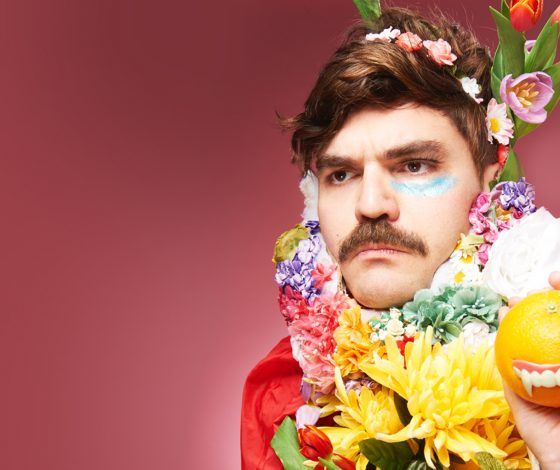 Closeup of a young moustachioed man wearing a flower garland and flowers in his hair looking off to the left and holding an orange with false teeth on the front of it