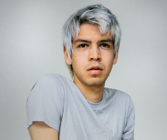 Male comedian with grey hair in a grey t-shirt against a grey background. Grey.