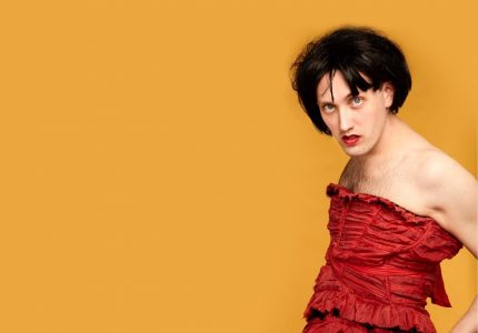 Male comedian in red frilled dress and black wig, against orange background.