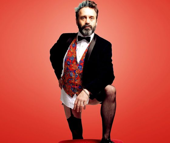 breaded man in a suit and tie top, no trousers and wearing stockings ans suspenders with mens shoes, red background