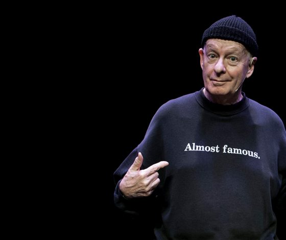 elder man in a beanie hat points to his sweather which has the words ' almost famous' on the front. black background