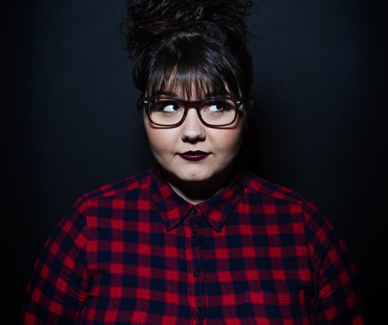 Woman in glasses and checked shirt facing fowards