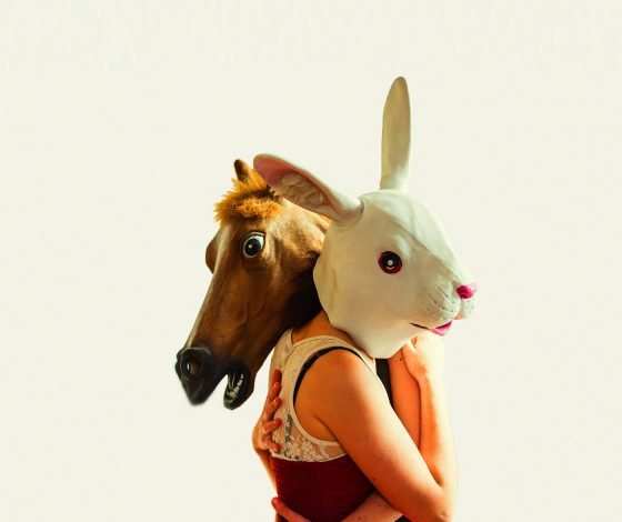 a man wearing a horse-head mask embraces a woman with a rabbit-head mask