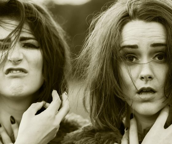 black and white close up of two young women with tousled hair, one with a leery defiant expression, the other startled