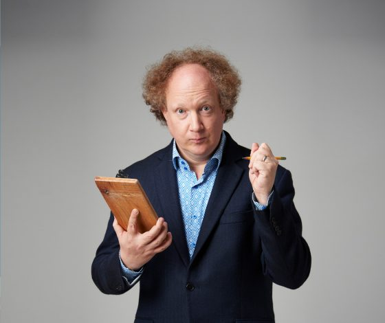 a middle aged man with fuzzy red hair and a bald crown in a dark blue jacket and blue shirt holds a clipboard and pen, with an eyebrows raised expression