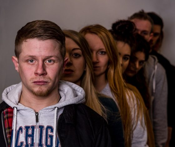 A line of sombre actors behind a young man in a hoody.