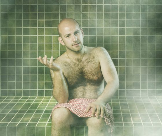 a bald young man wearing a red checked cloth around his lap sits in a green tiled sauna, gesturing with his hand