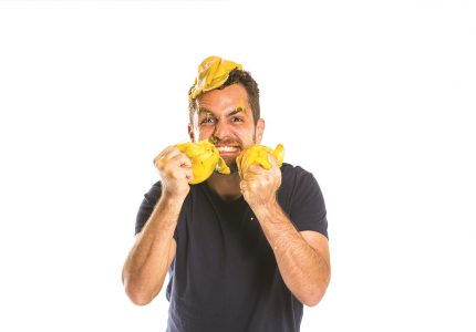 a man in a t-shirt mock-angrily stands squishing mangoes in his hands which are held up near his face, squished mango also on his head