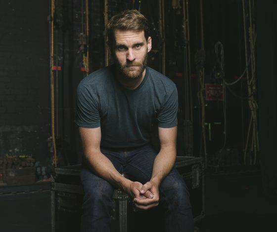 Bearded man in dark t-shirt with hands clasped in front of him.