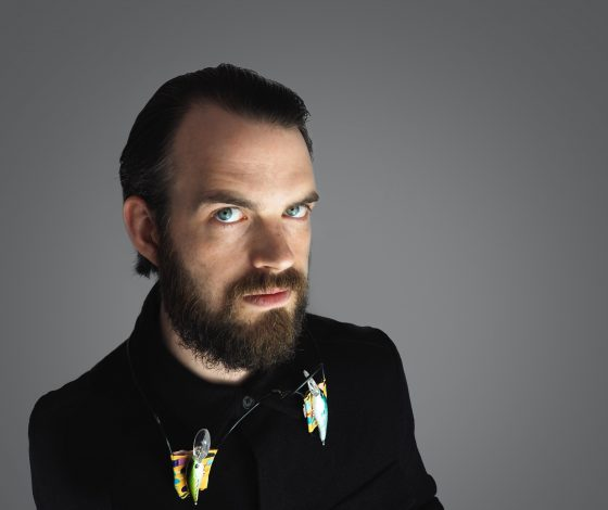 A bearded man in a black shirt and a couple of fishing floats strung near his neck gazes up intently at the camera
