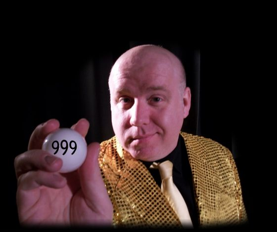 Marcus Hendry in a glittering old blazer and black shirt, holding up a white balll with the numbers '999'