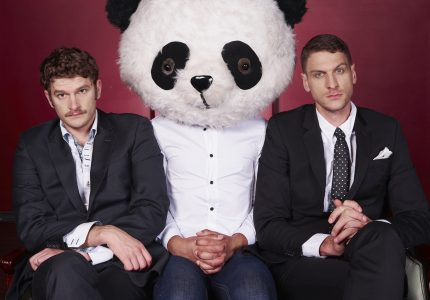 two men wearing suits and rocking deadpan expressions looks into the camera, each sat either side of a man wearing a large panda headmask in the middle of them