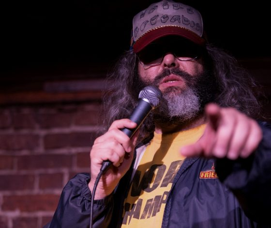 A man with a speckled grey shaggy beard wearing spectacles and a baseball cap holds a microphone with one hand and points directly at the camera with the other