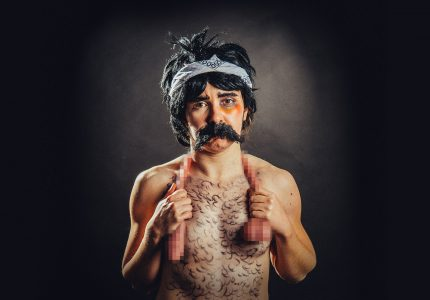 a woman presenting as a man, bare torso with drawn on chest hair, fake moustache, clutchingh at each end a long dildo slung around the neck area