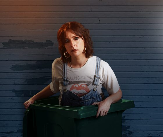 A young red-haired woman wearing a t-shirt under denim dungarees, with hoop earrings and a stern expression, emerges from a swing bin