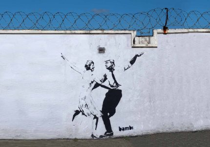 a whitewashed perimiter wall with barbed wire across the top. centrally on the wall a banksy-style stencilled graffiti of Therea May and Donald Trump dancing together with their arms extended.
