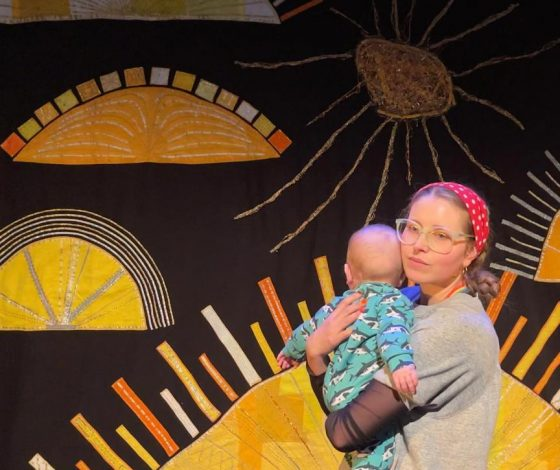 Jessie Cave holding a baby in front of Sunrise set