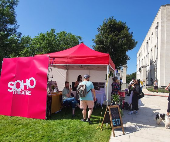 People in and around a Soho Theatre pink tent in a square on a sunny day