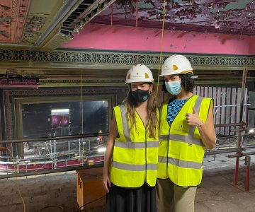 two young women wearing high visibility vests, hard hats and masks, stand together inside a theatre